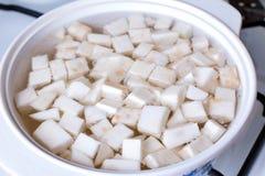 Cubos da raiz de aipo na água a ferver Foto de Stock