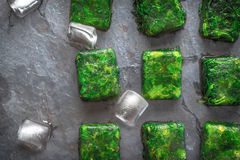 Cubos de espinafres congelados com os cubos de gelo na opinião de tampo da mesa de pedra Fotos de Stock Royalty Free