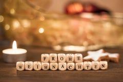 Cubos de Frohe Weihnachten na frente do fundo obscuro do Natal Foto de Stock