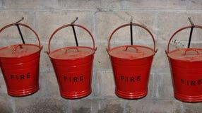 Cubos de fuego rojo que cuelgan en la pared Fotografía de archivo libre de regalías