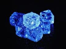 Cubos de gelo azulados transparentes em um fundo preto Imagens de Stock Royalty Free