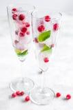 Cubos de gelo com bagas e a hortelã vermelhas nos vidros no fundo branco Imagens de Stock