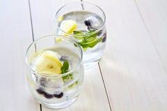 Cubos de gelo com fruta em um vidro da água Imagens de Stock Royalty Free