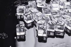 Cubos de gelo em um fundo preto Fotografia de Stock
