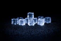 Cubos de gelo molhados no fundo preto Fotografia de Stock Royalty Free