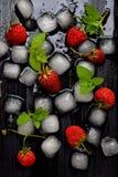 Cubos de gelo, morangos e folhas de hortelã em um fundo de madeira preto Fundo do alimento Configuração lisa Imagem de Stock Royalty Free