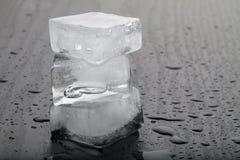 Cubos de gelo no fundo preto da tabela fotos de stock