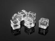 Cubos de gelo plásticos refletidos na superfície textured Imagem de Stock