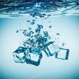 Cubos de gelo que caem sob a água Imagens de Stock