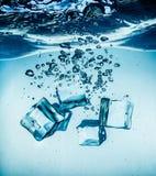 Cubos de gelo que caem sob a água Imagem de Stock Royalty Free