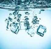 Cubos de gelo que caem sob a água Imagens de Stock Royalty Free