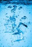 Cubos de gelo que caem sob a água Fotografia de Stock Royalty Free