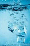 Cubos de gelo que caem sob a água Imagem de Stock