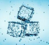 Cubos de gelo que caem sob a água Fotografia de Stock