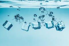 Cubos de gelo que caem sob a água Foto de Stock