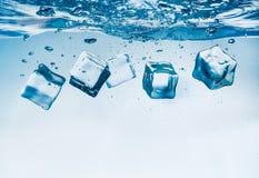 Cubos de gelo que caem sob a água Fotos de Stock