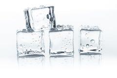 Cubos de gelo transparentes com gotas da água isolados no fundo branco Fotos de Stock