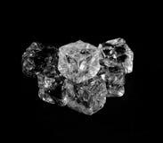 Cubos de gelo transparentes em um fundo preto Foto de Stock Royalty Free