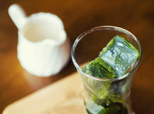 Cubos de hielo del té verde de Matcha con leche fresca en la tabla de madera Imagen de archivo