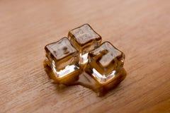 Cubos de hielo en el escritorio de madera Imagen de archivo libre de regalías