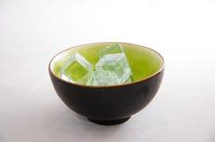 Cubos de hielo en un tazón de fuente verde Fotos de archivo libres de regalías