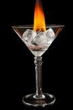 Cubos de hielo en vidrio con la llama en superficie negra brillante Foto de archivo libre de regalías