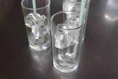 Cubos de hielo en vidrio con la paja en la tabla imagen de archivo libre de regalías