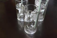 Cubos de hielo en vidrio con la paja en la tabla fotos de archivo libres de regalías