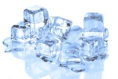Cubos de hielo frescos que derriten en una superficie reflexiva Foto de archivo libre de regalías