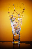 Cubos de hielo que salpican en el vidrio de agua Imagenes de archivo