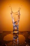 Cubos de hielo que salpican en el vidrio de agua Fotos de archivo libres de regalías