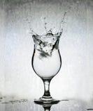 Cubos de hielo que salpican en el vidrio de agua, aún vida, parte posterior del Grunge Imagen de archivo