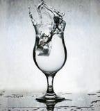 Cubos de hielo que salpican en el vidrio de agua, aún vida, parte posterior del Grunge Fotos de archivo