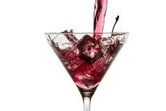 Cubos de hielo y licor rojo en un vidrio de martini Foto de archivo libre de regalías