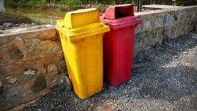 Cubos de la basura amarillos y rojos vivos sucios en la calle además de la pared Fotografía de archivo libre de regalías