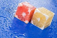 Cubos de la fruta cítrica en superficie azul Imágenes de archivo libres de regalías