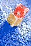 Cubos de la fruta cítrica en superficie mojada Fotografía de archivo libre de regalías
