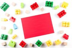 Cubos de madeira coloridos e blocos plásticos da construção com o cartão de papel vazio vermelho no fundo branco fotografia de stock