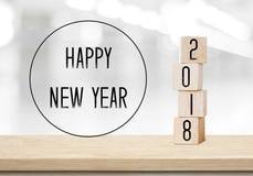 Cubos de madeira com 2018 e ano novo feliz sobre o backgr do bokeh do borrão Foto de Stock Royalty Free