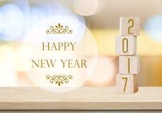 Cubos de madeira com 2017 e ano novo feliz sobre o backgr do bokeh do borrão Imagem de Stock