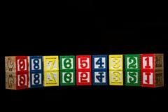 Cubos de madeira com números isolados no fundo preto Imagem de Stock