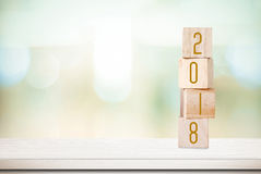 Cubos de madeira com o 2018 na tabela sobre o fundo do bokeh do borrão com Foto de Stock