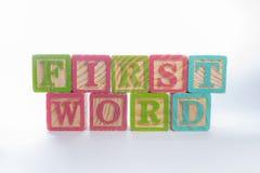 Cubos de madeira da primeira palavra imagens de stock
