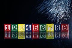 Cubos de madeira e números isolados no fundo preto Fotos de Stock