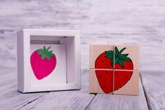 Cubos de madeira ecológicos com frutos Figuras geométricas coloridas no fundo de madeira Fotos de Stock Royalty Free