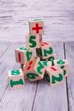 Cubos de madeira ecológicos com números Figuras geométricas coloridas no fundo de madeira Foto de Stock
