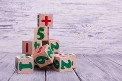 Cubos de madeira ecológicos com números Figuras geométricas coloridas no fundo de madeira Fotos de Stock Royalty Free