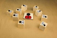 cubos de madeira sob a forma dos chefes e dos subordinados, subordina??o dos pessoais em um fundo azul fotografia de stock