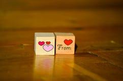 Cubos de madera con la inscripción escrita mano del corazón con el corazón rojo y rosado Imágenes de archivo libres de regalías