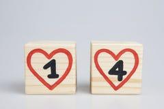 Cubos de madera con los corazones manuscritos del rojo del interior del número uno y cuatro Fotografía de archivo libre de regalías